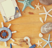 Collection of nautical and beach objects creating a frame over wooden background, Stock Images