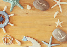 Collection of nautical and beach objects creating a frame over wooden background, Stock Photo