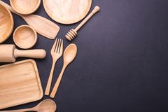 Collection of new wooden kitchen utensil, bowl, plate, spoon, di. Sh. Studio shot on black table background. With free space for text or design Royalty Free Stock Photography