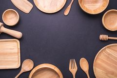 Collection of new wooden kitchen utensil, bowl, plate, spoon, di. Sh. Studio shot on black table background. With free space for text or design Stock Images