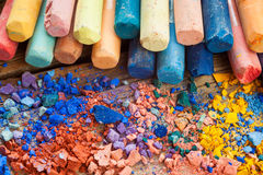 Collection Of Rainbow Colored Pastel Crayons With Crushed Chalk Stock Image