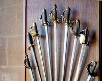 Collection of old antique sword,rapier and cutlass handles displayed on a wooden panel.  stock images
