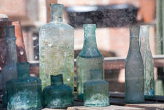 Collection of old green bottles on shelf Royalty Free Stock Photography