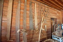 Collection of old saws hung on a wall. Old hand saws in various sizes, for milling large logs. Collection is hung on a wooden wall. Also shown is various farming royalty free stock images