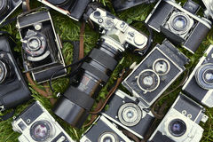 Collection of old vintage retro film analogue cameras. Lying on green grass lawn Royalty Free Stock Images