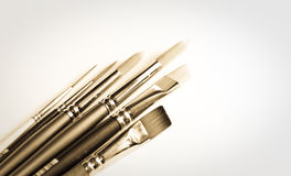 Collection of paintbrushes. A sepia toned collection of artist's paintbrushes with white background royalty free stock photography