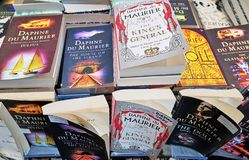 Collection of Paperback Books by Daphne Du Maurier. Cornwall, England - Aug 2016: Closeup of display of Daphne Du Maurier paperback books on a table in a stock photography