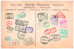 Collection of passport stamps on a vintage postcard Stock Photo