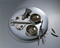 Collection of personal items. A view of a collection of several personal items including scissors, gloves, and jewelry, resting on a round disk Royalty Free Stock Photography