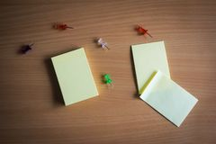 Collection of pins and note paper bunch and loose papers on wooden board. top view ready to fill your text and design quotes. Collection of pins and note paper Stock Image