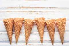 Collection plate de cornets de crème glacée de configuration sur le fond en bois blanc Images stock