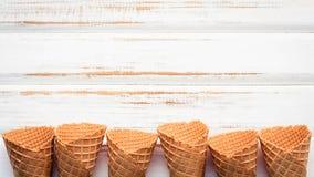 Collection plate de cornets de crème glacée de configuration sur le fond en bois blanc Photographie stock libre de droits
