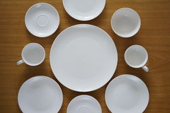 Collection of porcelain plains on wooden table Royalty Free Stock Photography