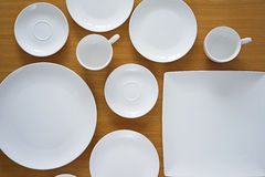 Collection of porcelain plains on wooden table Royalty Free Stock Images