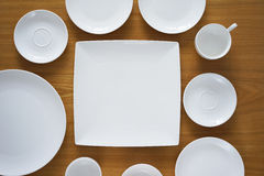 Collection of porcelain plains on wooden table Stock Images