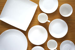 Collection of porcelain plates on wooden table Stock Photos