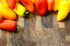 A collection of Red and Yellow Sweet Peppers Bordering Wood Cutt Royalty Free Stock Image