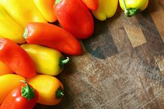 A collection of Red and Yellow Sweet Peppers Bordering Wood Cutt. A collection of fresh, red, yellow, and orange sweet peppers are bordering a wooden cutting Stock Images