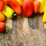 A collection of Red and Yellow Sweet Peppers BorderingWood Cutti Royalty Free Stock Photo