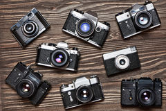 Collection of retro SLR cameras on wooden background Royalty Free Stock Photography