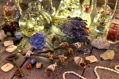 Collection rituelle magique avec des bouteilles, des fleurs de lavande, le pentagone étoilé, des runes et des cristaux photos stock