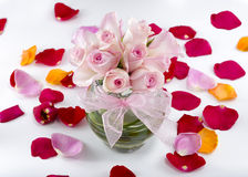 Collection of rose petals with a vase of pink roses in the middl Royalty Free Stock Photo
