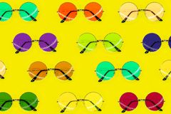 Collection of round multicolored sunglasses. Summer pattern on yellow background. Fashion collection. Sunglasses for tropical trip stock photo