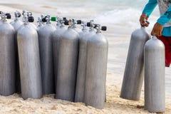 Collection of Scuba Diving Air Tanks. A collection of scuba divers air taks on a tropical white sand beach stock photos