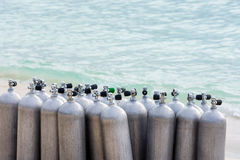 Collection of Scuba Diving Air Tanks. A collection of scuba divers air taks on a tropical white sand beach stock images