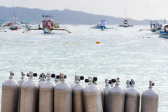 Collection of Scuba Diving Air Tanks. A collection of scuba divers air taks on a tropical white sand beach with depth of field back ground of calm sea and pump stock images