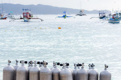 Collection of Scuba Diving Air Tanks. A collection of scuba divers air taks on a tropical white sand beach with depth of field back ground of calm sea and pump stock photo