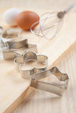 Collection of Cookie cutter forms with flour on wooden board Royalty Free Stock Images