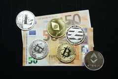 Collection of silver and gold cryptocurrency coins on a 50 euro banknote stock images