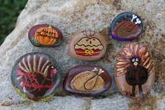 Collection of six small rocks painted for Thanksgiving. Six small rocks are painted in a Thanksgiving theme. There are turkeys, both roasted and living, a royalty free stock photography