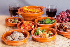 Collection of spanish tapas foods in terracotta bowls. Stock Images