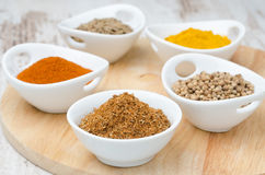 Collection of spices in white bowls on the wooden board Stock Image