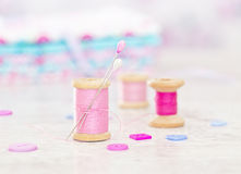 Collection of spools  threads in pink colors arranged on a white wooden background Royalty Free Stock Images