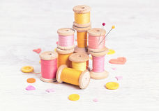 Collection of spools  threads in yellow-red colors arranged on a white wooden background Stock Images