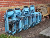 Stacked blue chairs of a terrace in springtime. A collection of stacked blue chairs of a terrace in springtime Royalty Free Stock Photos