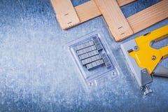 Collection of stapler gun metal staples wooden plank on metallic Stock Images