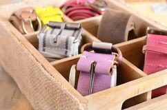 Collection of stylish belts in wooden crate Royalty Free Stock Photo