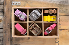 Collection of stylish belts in wooden crate Royalty Free Stock Photography