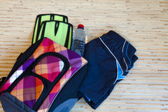 Collection of swimming equipment. Flippers, cap, spilling out of the bag on the background for the school swim team background or competitive swim teams. The royalty free stock photo