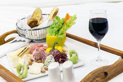 Collection of tasty cheese and ham served in a tray on a bed Stock Images