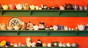 Collection of teapots on shelf. A collection of different sized teapots on green shelves against an orange background Royalty Free Stock Photography