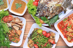 Collection of thai food on wood floor,papaya salad (SOM TUM),Spi. Cy Grilled Pork Salad and Grilled Fish in the food has been popular in Thailand Royalty Free Stock Photos