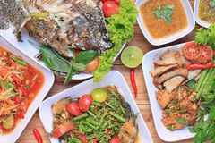 Collection of thai food on wood floor,papaya salad (SOM TUM),Spi. Cy Grilled Pork Salad and Grilled Fish in the food has been popular in Thailand Royalty Free Stock Image