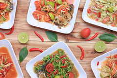 Collection of thai food on wood floor,papaya salad (SOM TUM),Spi. Cy Grilled Pork Salad and Grilled Fish in the food has been popular in Thailand Royalty Free Stock Photo