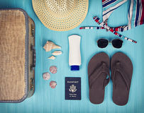 A collection of travel items. Including suitcase, passport, sandals, sunglasses, swim suit, sunscreen and straw hat on turquoise background royalty free stock photos
