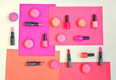 Various lipsticks, nail polishes and macaroons. Collection of various lipsticks, nail polishes and macaroons on colorful paper background Royalty Free Stock Photo